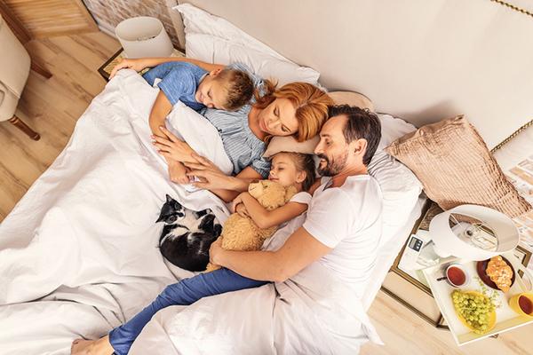 Una familia en la cama con su gato.